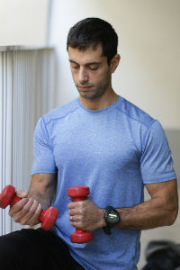 תמונה של מאמן כושר אישי מחזיק משקולות יד אדומות