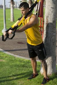 מאמן מבצע תרגיל באמצעות רוצועות trx