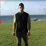 בחור אוחז משקולת מתוך פוסט וידאו כיצד לבצע כפיפת מרפק