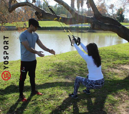 מאמן כושר ומתאמנת בפארק מבצעים תרגיל עם רצועות
