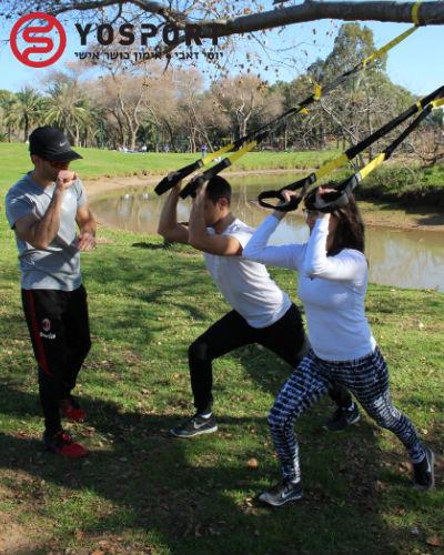 מאמן כושר מאמן זוג בפארק עם רצועות TRX