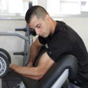 מאמן כושר מכווץ יד עם משקולת מתוך פוסט כיצד לבנות שרירים - cluster set שיטת האימון שלא הכרתם