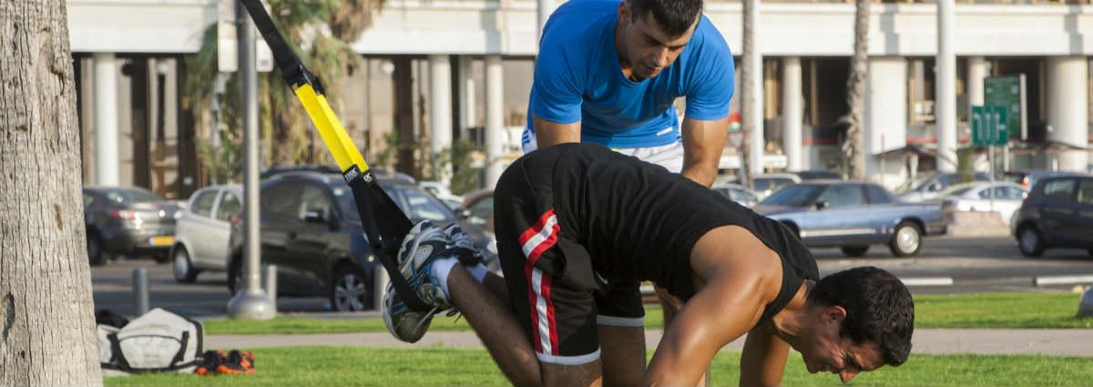 בחור עם רצועות אימון מבצע תרגיל לבטן בפארק