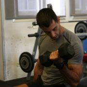 מאמן כושר עם משקולת מתוך מאמר 5 סיבות מעולות מדוע כדאי לכם להוריד משקלים בחדר הכושר