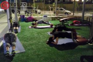 קבוצה של נשים בלילה מבצעות תרגיל לבטן על מזרנים בגינה