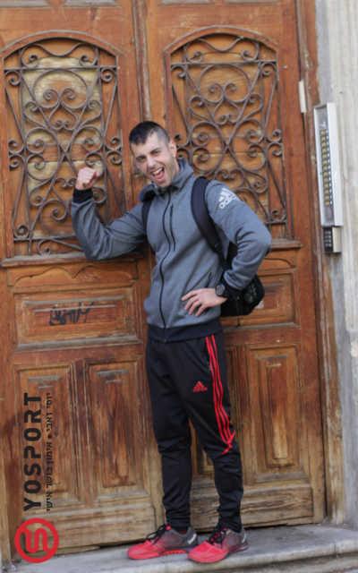 מאמן כושר על מפתן דלת עץ גדולה וחומה