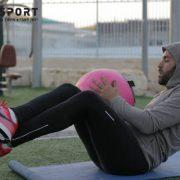 מתאמן עם כדור מבצע תרגיל לבטן בגינה
