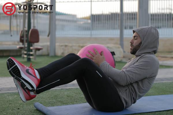 מתאמן שמבצע תרגיל עם כדור