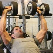 מאמן כושר מבצע לחיצת חזה - תרגיל רב מפרקי